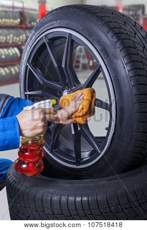 Mechanic Cleaning The Rim Of Tire