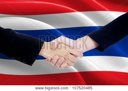 Two Politicians Shaking Hands With Flag Of Thailand