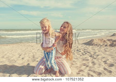 Mother And Daughter Having Fun Playing On The Beach