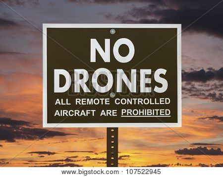 No drones sign with sunset sky.