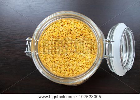 Dried yellow lentils in a glass jar on the table