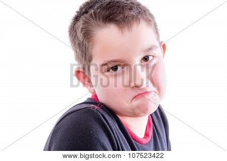 Portrait Of Boy Frowning In White Studio