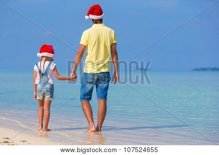 Little girl and happy father in Santa Hat during beach Christmas vacation