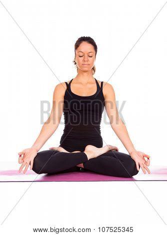 Beautiful woman doing Lotus of Padmasana or Kamalasana pose on yoga class. Studio shot.