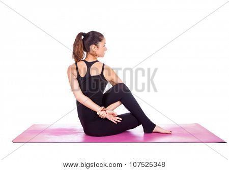Beautiful woman doing Eka Pada Upavisha Parivrttasana pose on yoga class. Studio shot.