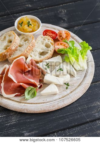 Ham, Cheese, Tomatoes And Ciabatta Bread Served On A Light Wooden Board On A Dark Wooden Surface. Ta