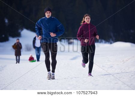 healthy young couple jogging outside on snow in forest. athlete running on  beautiful sunny winter d