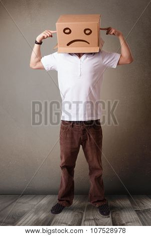Young man standing with a brown cardboard box on his head with sad face