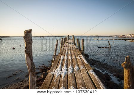 Wooden Pier In Snow At The Sea, Norway