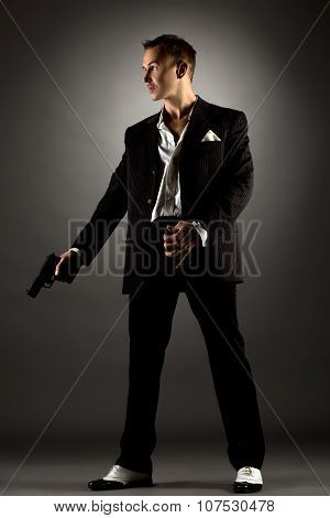 Handsome man dressed as gangster holding gun