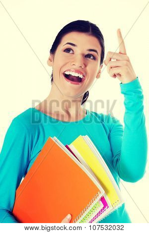 Young happy female student is pointing up and holding workbooks.