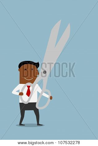 Happy businessman with huge scissors