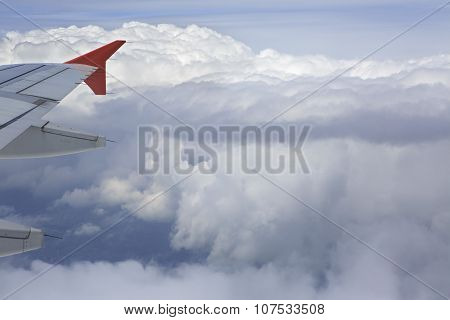 Wing aircraft and cumulus clouds in the sky above earth.