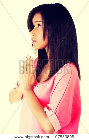 Young pretty adult woman praying.