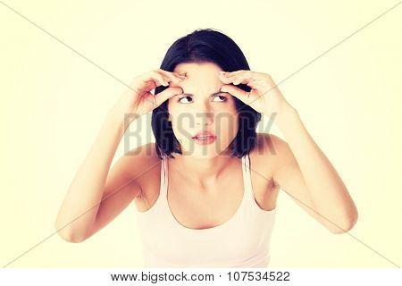 Beautiful shocked woman checking her first wrinkles on forehead