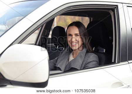 smiley young woman driving the car and smiling