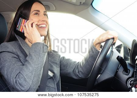 cheerful young woman driving a car and talking on the smartphone