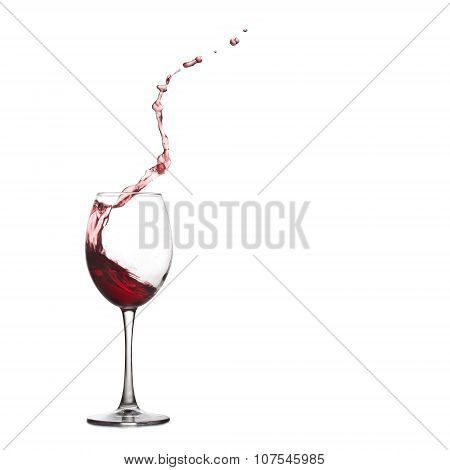 Wine glass splash and drops. Pouring red dry, splashing into crystal glass, close-up, white backgrou