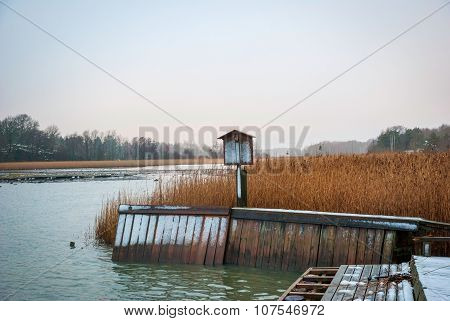 Pier And Dry Grass By The Fjord In Winter