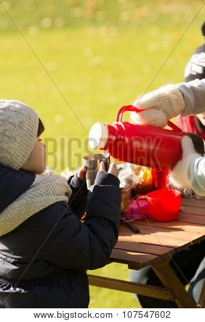 A little kid holding a cup while her mother pouring tea