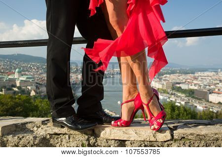Beautiful couple legs, red dress, and city view