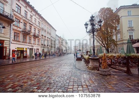Rainy weather at central Market Square with lamposts and cobbled streets