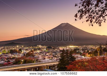 Mt. Fuji rises over Fujiyoshida, Japan in autumn.