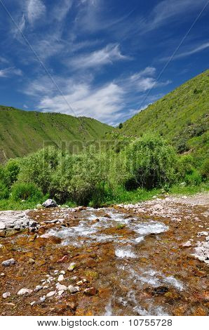 Colorful river in mountains with sky and clouds