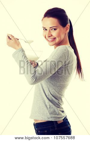 Young casual woman eating a yoghurt