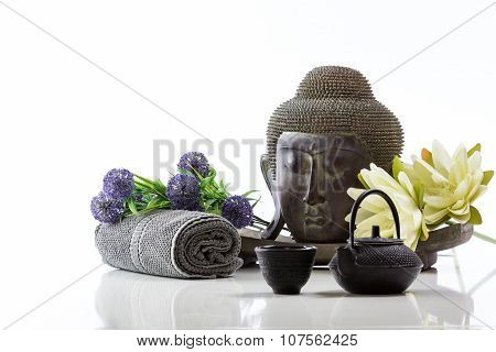Buddha head on a white background, towel, teapot and lotus