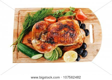 poultry : homemade roast turkey with greek olives and tomatoes on wooden board isolated over white background