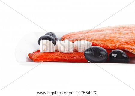 fresh grilled salmon meat fillet with goat light greek feta cheese black olives and tomatoes over long white plate isolated on white background
