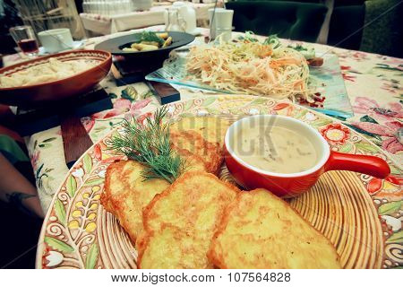 Potato Fritters With With Mushroom Sauce On A Dining Table