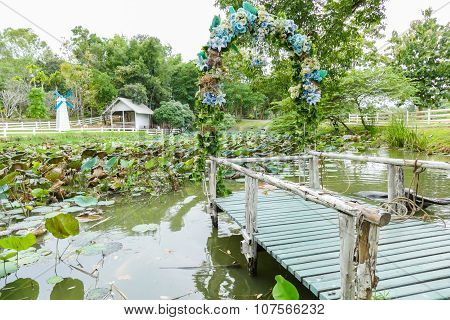 View Of The Wooden Pier Decorating With Blue Flower And Water Lily In The Pond