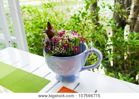 Fake Purple Flower In Blue Ceramic Cup On White Wooden Table Near The Window