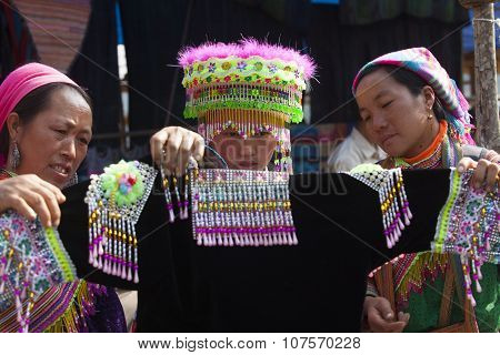 Vietnamese Hmong minority girl trying new traditional costume and a colorful traditional hat