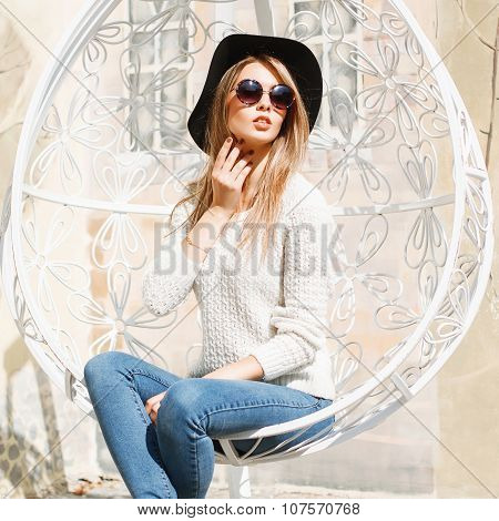 Portrait Of A Beautiful Girl In A Black Hat And Round Sunglasses. Relaxing On A White Suspended  Cha