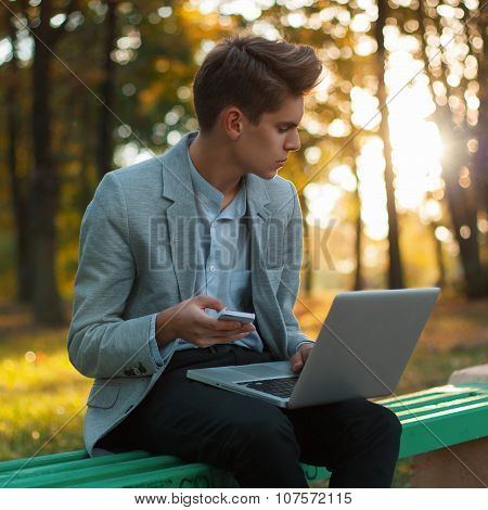Young Business Man Working With Laptop And Cellphone, Outdoors. Beautiful Sunset In The Park