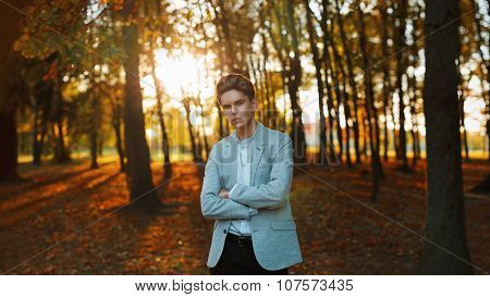 Young Handsome Guy In A Stylish Jacket And Shirt Standing At Sunset In The Park.