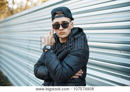 A Young Man In A Stylish Winter Jacket And Sunglasses On The Background Of A Metal Wall.