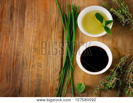 Olive Oil, Balsamic Vinegar And Herbs On A Vintage Wooden Background