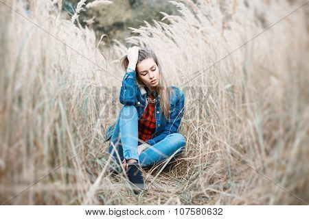 Pretty Girl Sits In A Beautiful Autumn Grass. Blue Jeanyoung Beautiful Girl With A Smile In Denim Cl