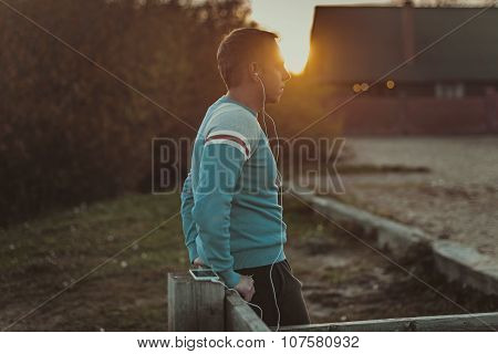 Attractive Man Sitting On  Beach In The Evening Sunset After Sport