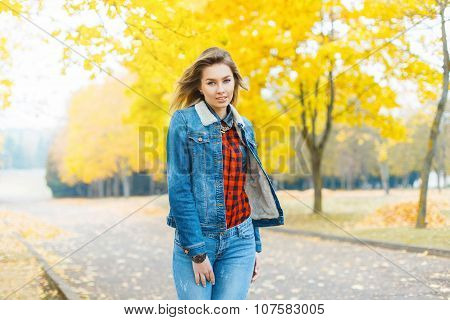 Pretty Girl In Jeans Clothes And A Red Checkered Shirt In Autumn Park.