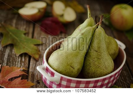 Green Pears In Pink Dish With Apples In Rustic Setting