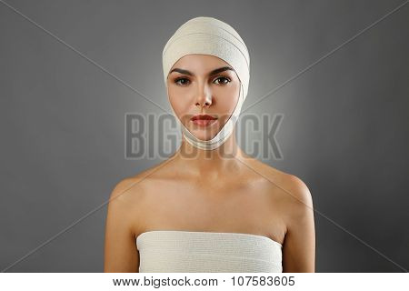 Young beautiful woman with an elastic bandage on her head and chest, on grey background