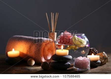 Beautiful spa composition with tender pink flowers on wooden table in the dark
