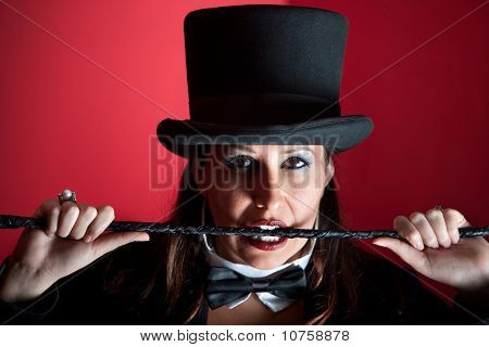 Woman In Top Hat Biting Whip