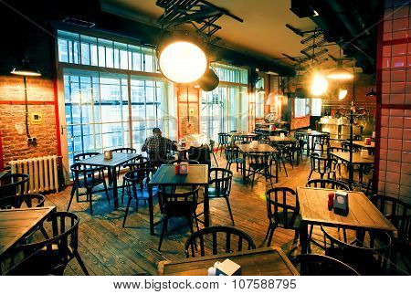 Lonely Man Sitting In Huge Room Of Empty Bar With Modern Design