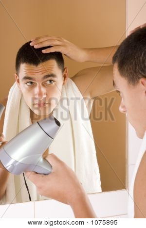 Young Man In The Bathroom'S Mirror Using Hair Drier